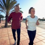 Mature Couple Jogging Together on Promenade --- Image by © Christoph Gramann/Corbis